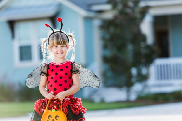 Young trick-or-treater in a lady bug costume
