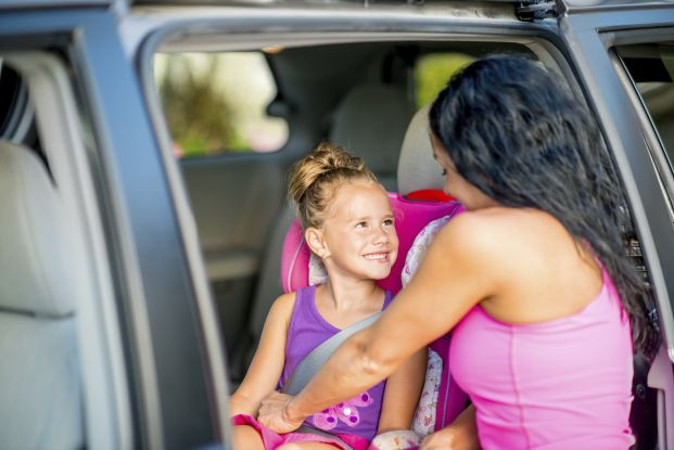 Woman putting young daughter in carseat.