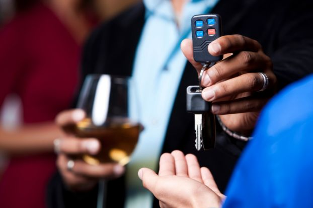 Man with glass of wine hands car keys to designated driver.